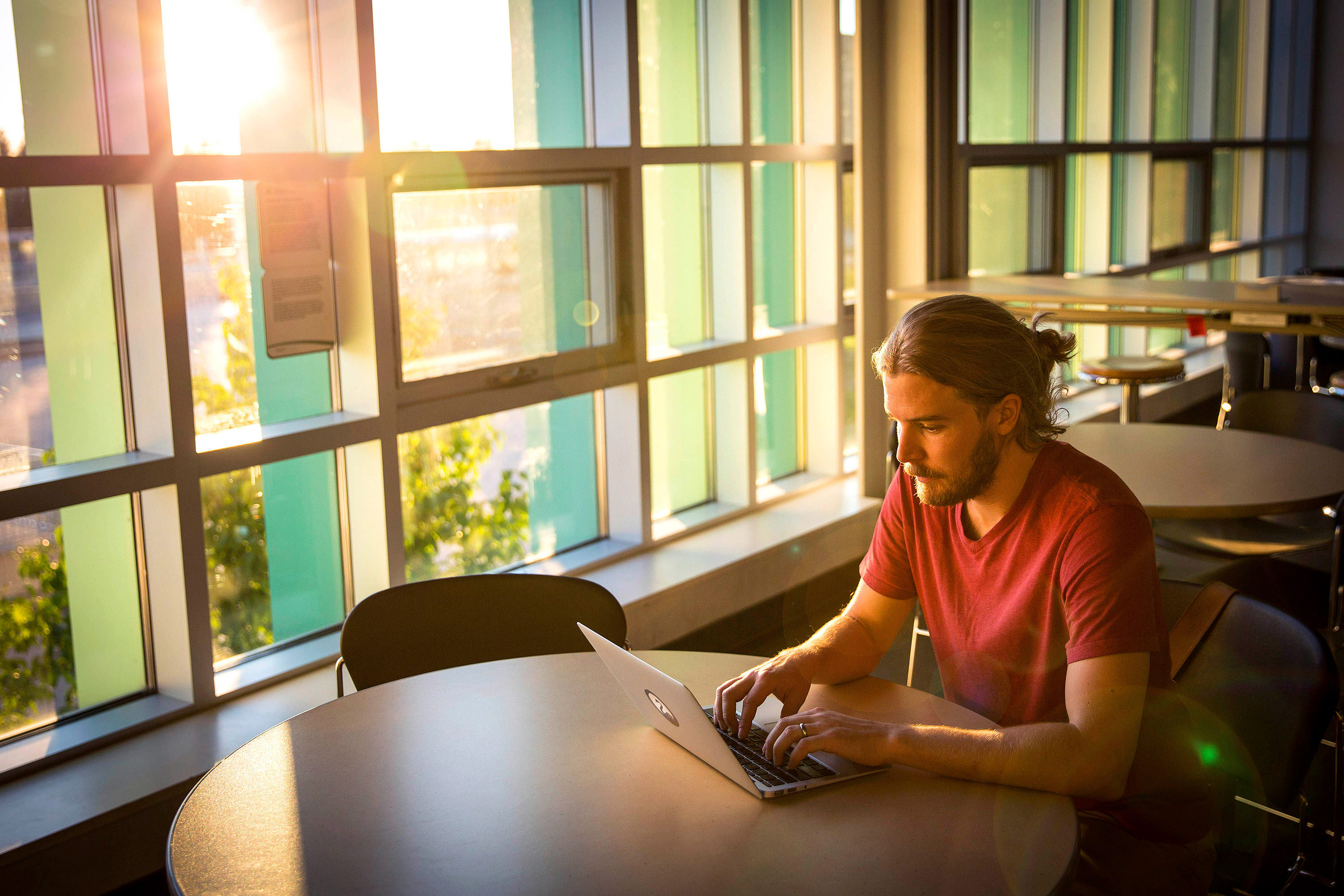 This is a picture of an Algonquin College student sitting with laptop.